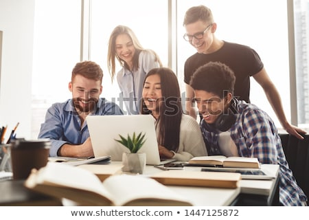 Cheerful group of young students sitting and studying Stock photo © deandrobot
