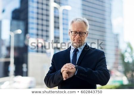 empresário · tempo · em · pé · escritório · entrada · olhando - foto stock © dolgachov