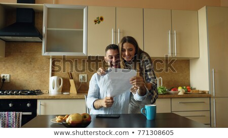 Woman opening letter at kitchen table Stock photo © IS2