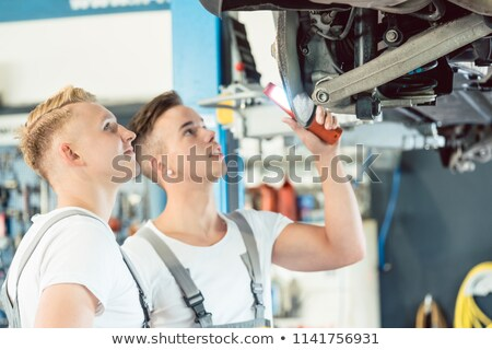 experienced auto mechanic teaching an apprentice about disk brakes stock photo © kzenon