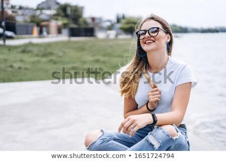 Mosolyog barna hajú nő póló ül kint Stock fotó © deandrobot