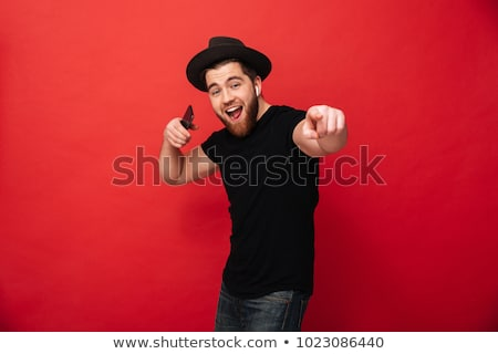 Portrait of a delighted man standing over red Stock photo © deandrobot