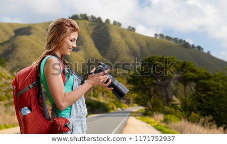 woman with backpack and camera over big sur hills Stock photo © dolgachov