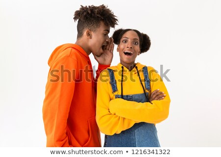 Photo of handsome african american man talking secrets in ear of Stock photo © deandrobot