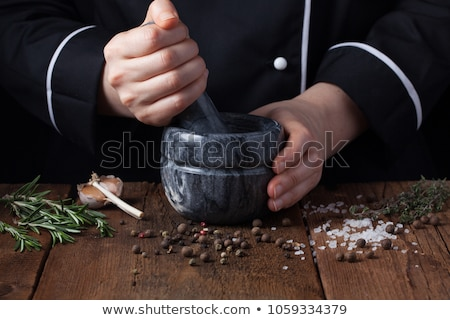 Black pepper in female hands on a background of spices Stock photo © galitskaya