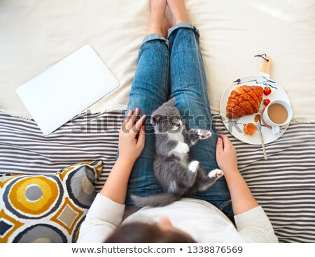 young woman with cute little kitten sitting on bed at home havin stock photo © dashapetrenko