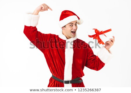 Image of amusing man 30s in santa claus costume and red hat hold Stock photo © deandrobot