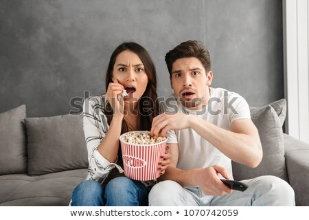 Portrait of tense man and woman sitting on sofa at home and look Stock photo © deandrobot