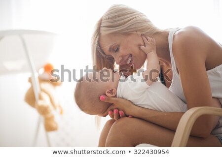 Young mother holding her newborn child on the chair Stock photo © Lopolo