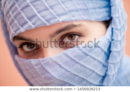Glance of young attractive muslim female in blue hijab gazing at you Stock photo © pressmaster