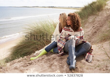 Two Teenage Girls Sitting In Sand Dunes Wrapped In Blanket stock photo © monkey_business