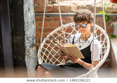 Contemporary young woman in casualwear and eyeglasses reading novel Stock photo © pressmaster