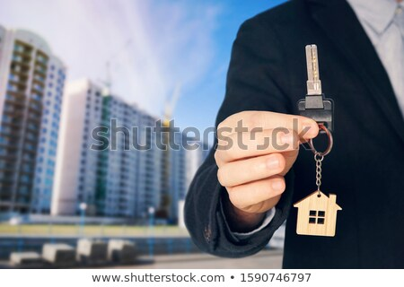 Man  Holding key in front of high rise apartments Stock photo © wavebreak_media