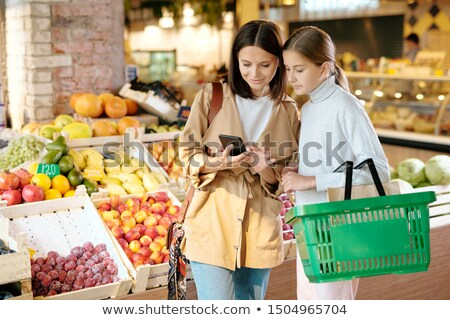 Woman with smartphone and her daughter scrolling through online assortment Stock photo © pressmaster