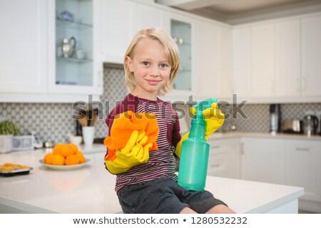 Boy holding rag and spray bottle in kitchen at home Stock photo © wavebreak_media