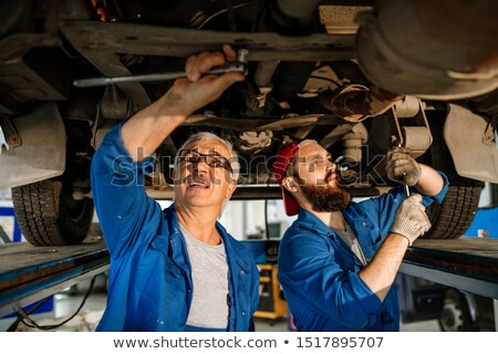 Young and mature technicians of car repair service fixing details of car motor Stock photo © pressmaster