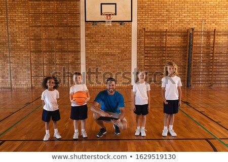 Front view of happy schoolkids and female coach looking at camera at basketball court in school Stock photo © wavebreak_media