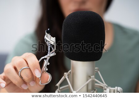 Woman Using Eyelash Curler On Microphone To Make Asmr Sounds Stock photo © AndreyPopov