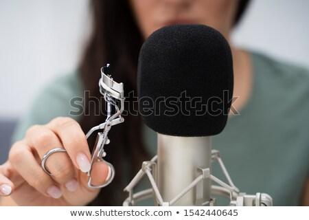 Woman Using Eyelash Curler On Microphone To Make Asmr Sounds Stock photo © AndreyPopov