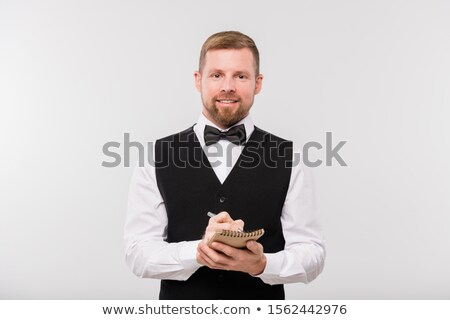 Happy young waiter in black waistcoat and bowtie writing down order in notepad Stock photo © pressmaster