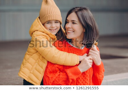 Photo of pleased attractive young mother looks positively at daughter, embraces mother, enjoy togeth Stock photo © vkstudio