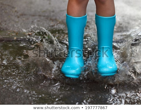 Stock photo: Child Wearing Blue Rain Boots Jumping Into A Puddl