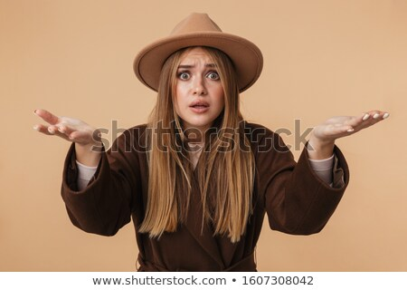 Image of young concerned girl wearing hat and coat reaching out  Stock photo © deandrobot