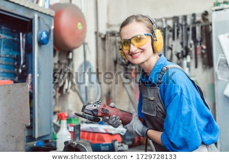 Woman mechanic working with disk grinder Stock photo © Kzenon