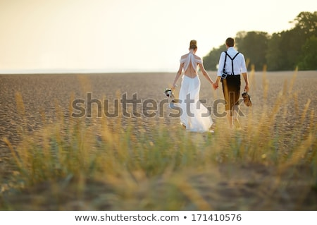 couples holding beautiful flowers bouquet together on the beach Stock photo © vichie81