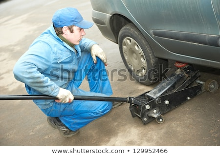 Stock photo: Serviceman unscrewing wheel in car workshop