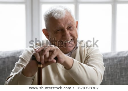 old man with a walking stick uses a smartphone Stock photo © nito