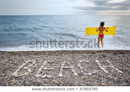 inscription from stones beach at stony coast young woman keeps stock photo © paha_l