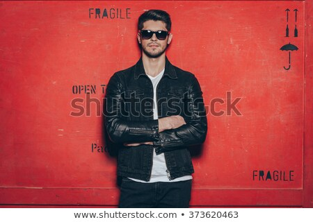 Man in leather jacket and jeans standing with arms crossed  Stock photo © deandrobot
