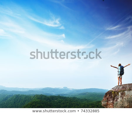 woman with backpack standing on cliffs edge and looking to a sky with clouds stock photo © zurijeta