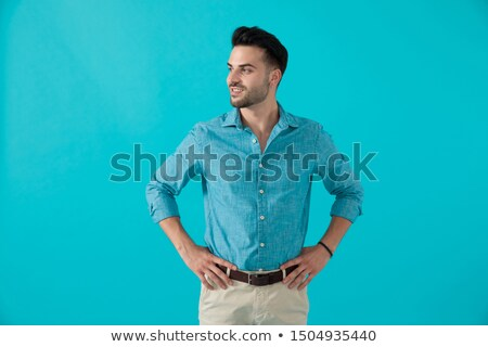 side of a casual man standing with hands on waist stock photo © feedough