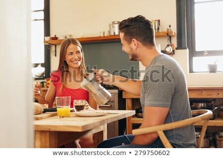 Man pouring coffee into cup of his girlfriend on kitchen Stock photo © deandrobot