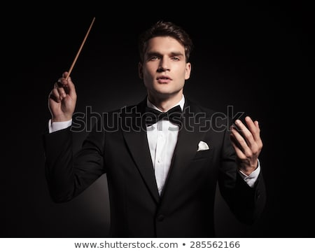 elegant man in tuxedo conducting an orchestra , business concept, on black studio background Stock photo © feedough