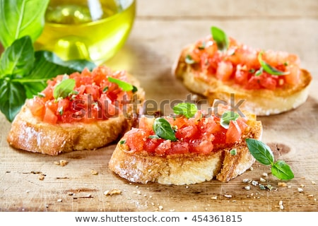 Tasty savory tomato Italian appetizers, or bruschetta, on slices of toasted baguette garnished with  Stock photo © frimufilms