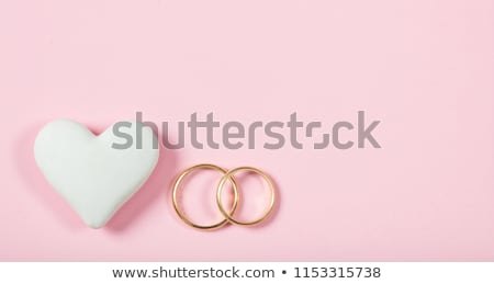 top view of golden wedding rings and pink hearts symbols isolated on white wedding rings background stock photo © lightfieldstudios