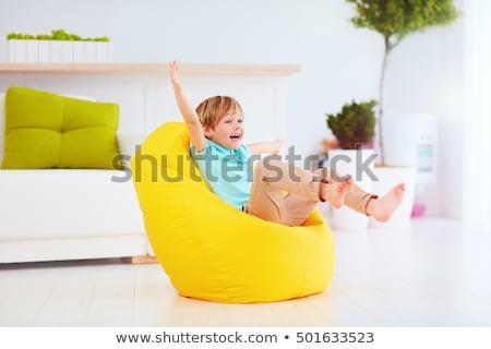 Criança sessão saco de feijão jovem sorridente vermelho Foto stock © LightFieldStudios