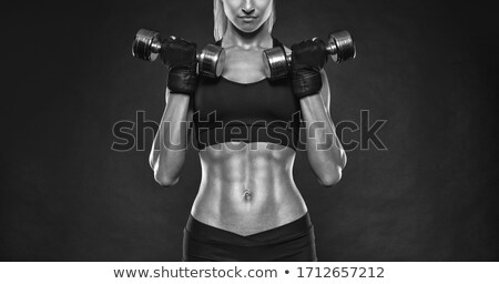 Studio photo of attractive female bodybuilder working out. Stock photo © arturkurjan
