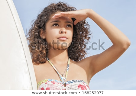 Woman with surfboard shielding eyes at beach Stock photo © wavebreak_media