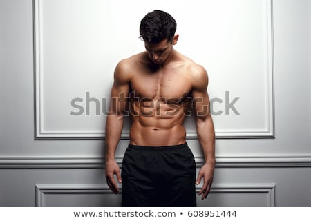 Portrait of a confident serious shirtless male bodybuilder Stock photo © deandrobot