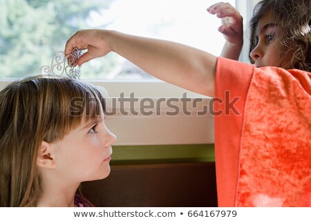 One girl putting tiara on another girl Stock photo © IS2