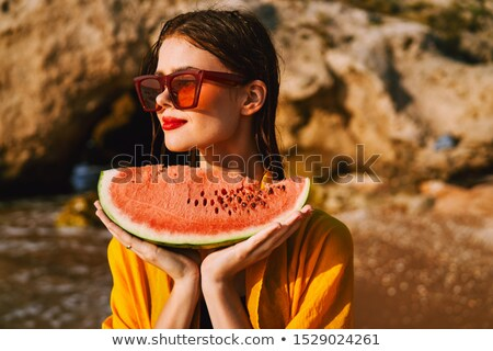 Girl in swimsuit with watermelon in hand and red background with seeds Stock photo © alphaspirit