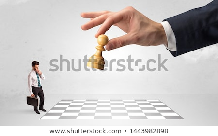 Little businessman playing chess with a big hand concept Stock photo © ra2studio
