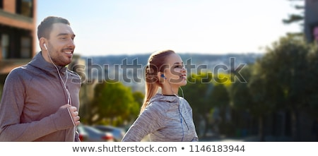 couple with earphones running over san francisco Stock photo © dolgachov