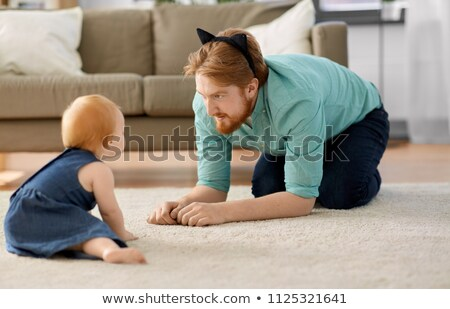 father wearing cat ears headband playing with baby Stock photo © dolgachov