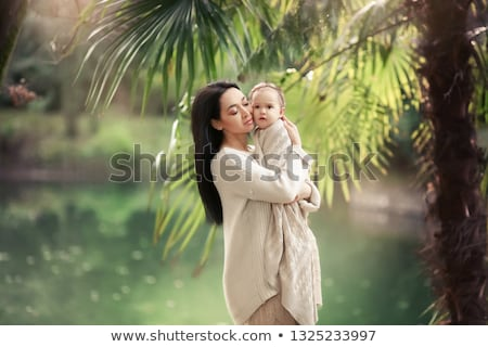 young and happy mother cares for her young son and walks along the shore of the lake in the summer stock photo © elenabatkova