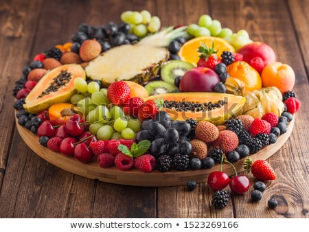Fresh raw organic summer berries and exotic fruits in round large tray on wooden kitchen background. Stock photo © DenisMArt